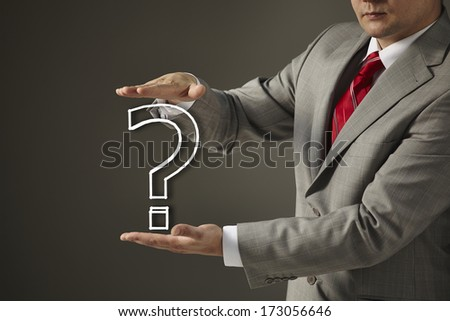 businessman in a black suit and tie holding a question mark. Concept of problem and solution