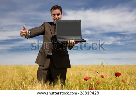 Businessman in a field showing his laptop