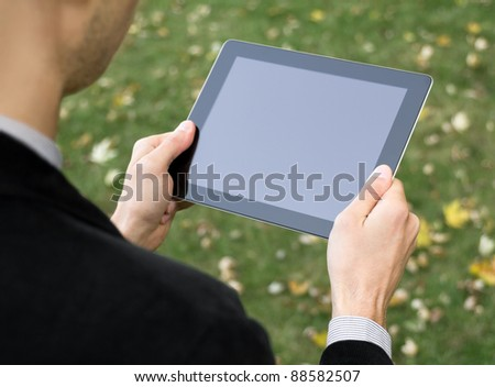 Businessman in a park holding a touch screen device.