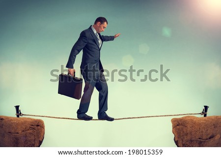 businessman in a predicament balancing on a tightrope