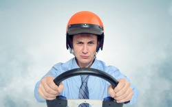 Businessman in a red helmet with steering wheel, car drive concept