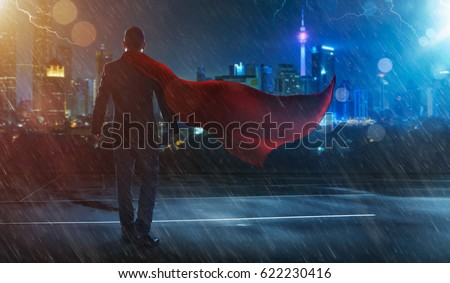 Businessman in a suit and cape hero facing a storm,victory concept. cityscape background , night scene . #622230416
