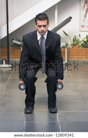 Businessman, in a suit, doing squats with dumbbells in a gym.