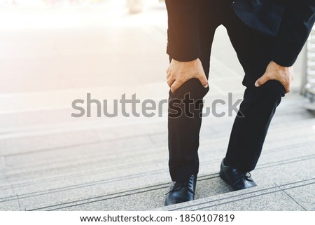 Businessman in a suit have the sore pain and painful knee problem expression and walk up and down on the stairway during go to office. Health care concept. Foto stock ©