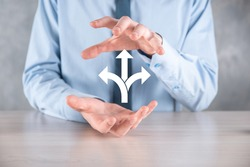 Businessman in a suit holds a sign showing three directions. in doubt, having to choose between three different choices indicated by arrows pointing in opposite direction concept. three ways to choose