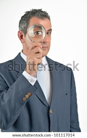 Businessman in a suit looking through a magnifying glass. Isolated on white