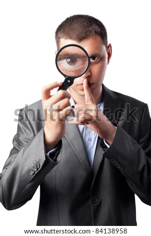 businessman in a suit looking through a magnifying glass isolated on white background