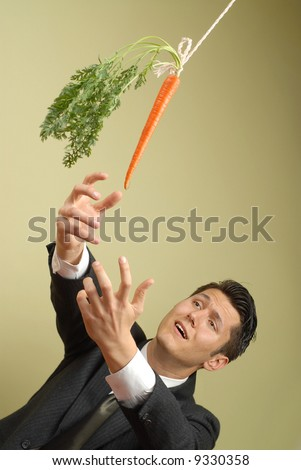 Businessman in a suit reaching for a carrot on a stick