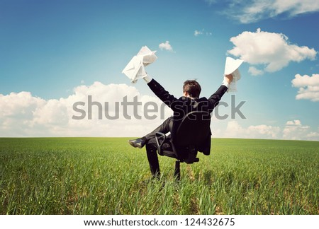 businessman in a suit sitting on a chair in a field and holding documents