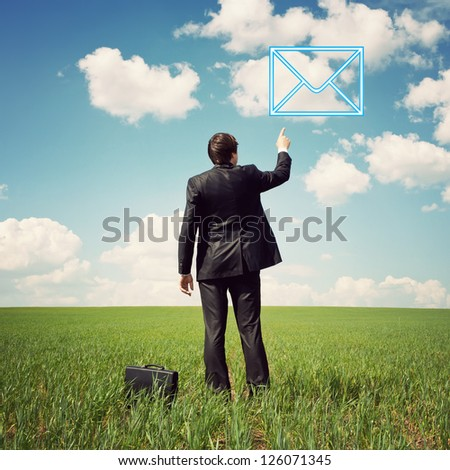 businessman in a suit standing in the field and points a finger at mail