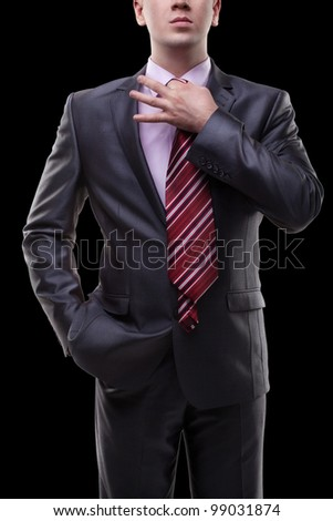 Businessman in a suit straightens his tie.