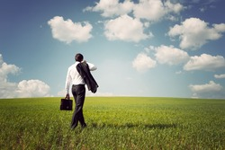 businessman in a suit with a briefcase walking on a spacious green field with a blue sky