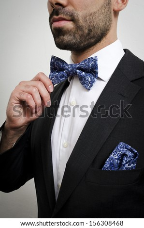 Businessman in a suit with pocket square and bow tie
