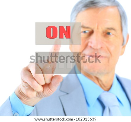 Businessman in age, click on the button. Isolated on a white background.