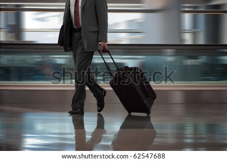 Businessman in airport with suitcase.