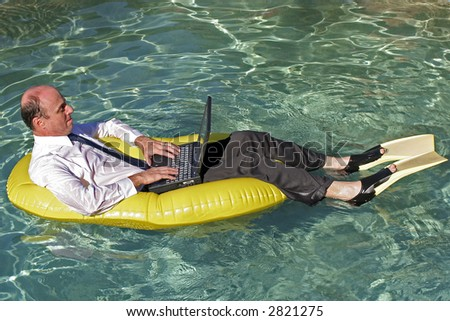 Businessman in an inflatable boat wearing his business suit and tie and also yellow flippers with his lap top on his lap with the crystal clear ocean all around him