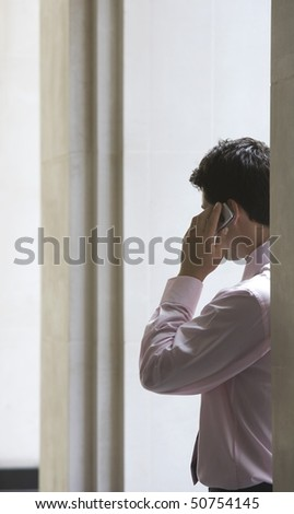 Businessman in archway talking on cell phone