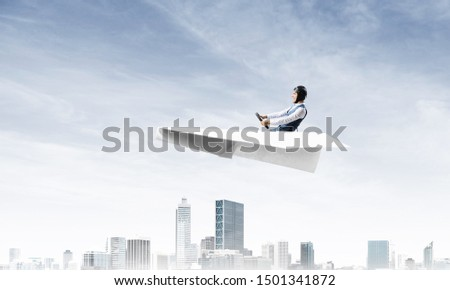 Businessman in aviator hat and goggles driving paper plane above downtown with high buildings. Modern megalopolis panorama with blue skyscape. Mixed media business concept. Dreaming and imagination. #1501341872