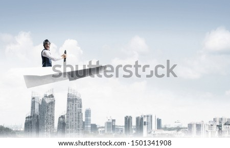 Businessman in aviator hat and goggles driving paper plane above downtown with high buildings. Modern megalopolis panorama with blue skyscape. Mixed media business concept. Dreaming and imagination. #1501341908