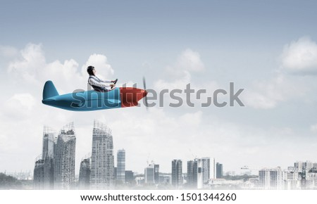 Businessman in aviator hat and goggles driving propeller plane above downtown with high buildings. Modern megalopolis panorama with cloudy skyscape. Mixed media business concept. #1501344260
