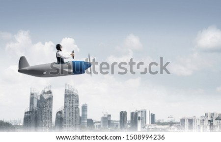 Businessman in aviator hat and goggles driving propeller plane above downtown with high buildings. Modern megalopolis panorama with cloudy skyscape. Mixed media business concept. #1508994236