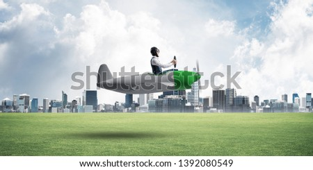 Businessman in aviator hat and goggles driving propeller plane. Downtown with high buildings. Man in airplane flying low above ground. Modern megalopolis panorama with green grass and cloudy sky #1392080549