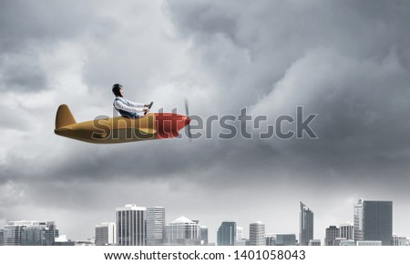 Businessman in aviator hat and goggles driving propeller plane in storm. Side view of pilot in small airplane. Megalopolis panorama with dramatic dark cloudy skyscape. Mixed media business concept. #1401058043