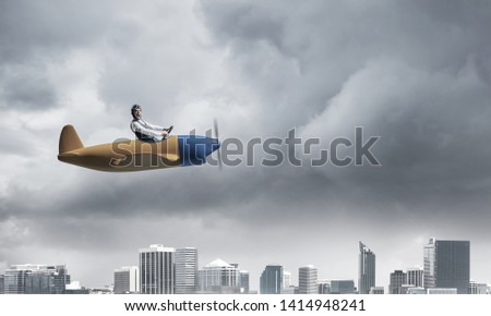 Businessman in aviator hat and goggles driving propeller plane in storm. Side view of pilot in small airplane. Megalopolis panorama with dramatic dark cloudy skyscape. Mixed media business concept. #1414948241
