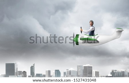 Businessman in aviator hat and goggles driving propeller plane in storm. Side view of pilot in small airplane. Megalopolis panorama with dramatic dark cloudy skyscape. Mixed media business concept. #1527431048