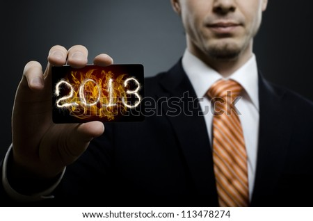 businessman in black costume and orange necktie reach out on camera and show credit card with date 2013, close up