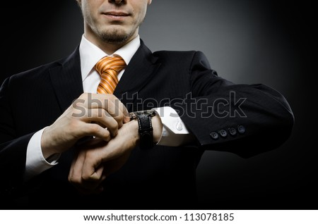 businessman in black costume wind clock (wristwatch) on hand