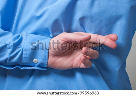 Businessman in black shirt crossing his fingers behind his back