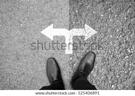 Businessman in black shoes standing at the crossroad making decision which way to go - easy or hard