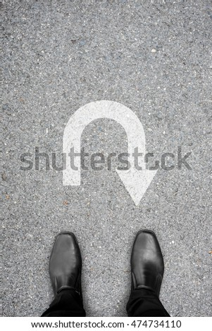 Businessman in black shoes standing on the asphalt concrete floor in front of u turn symbol