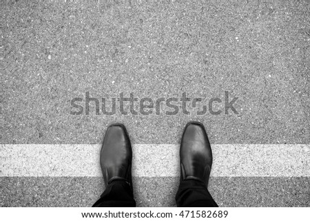 Businessman in black shoes standing on white line. Prohibited and restricted. Crossing border. Think different.