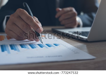 Businessman in black suit analyzes business data and working on laptop computer in office, business strategy  analysis, business profits review concept, close up