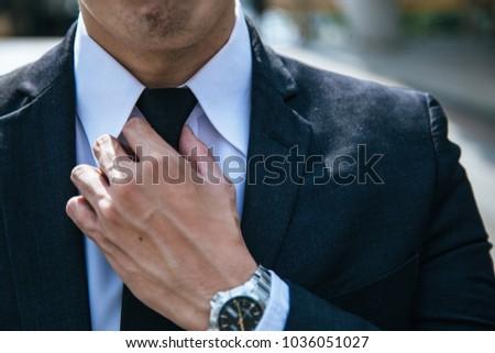 Businessman in black suit and adjusting his necktie. Stock foto ©