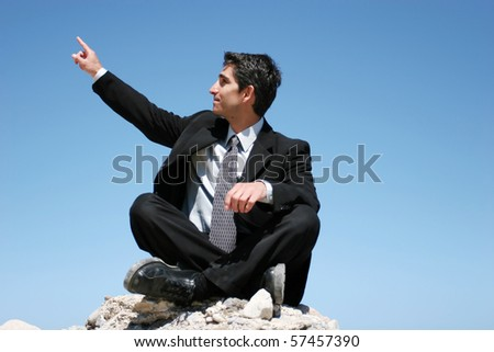 Businessman in black suit sitting on the rocks