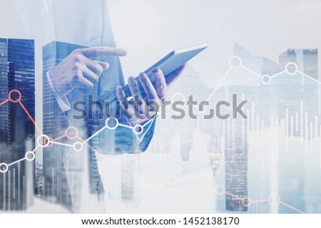 Businessman in black suit using tablet computer with double exposure of cityscape and graphs. Concept of stock market and trading. Toned image