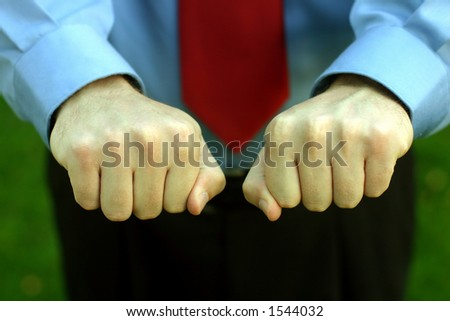 Businessman in blue shirt and red tie holds out both hands, closed as to give the viewer a choice as to which one he/she wants to open
