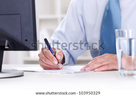 Businessman in blue shirt sitting at office desk signing a contract