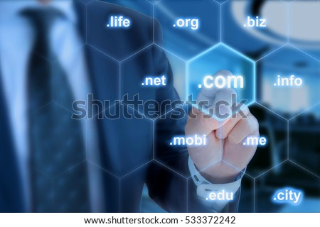 Businessman in blue touching the domain ending com on a hexagon grid in front of office background Stock photo ©