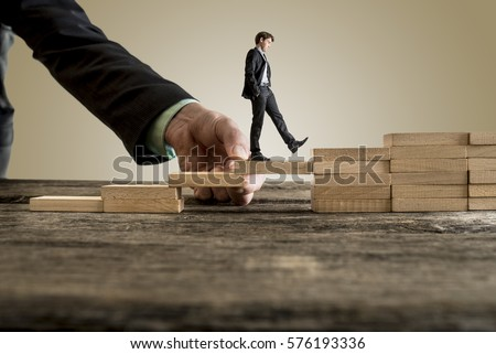 Businessman in business suit walking up steps, while the hand of other man helping him in a conceptual image of insurance, assistance and support.