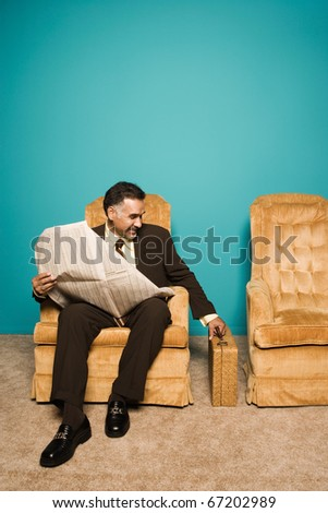 Businessman in chair with newspaper and briefcase - stock photo