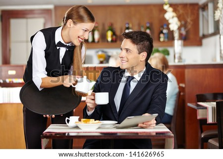 Businessman in coffee shop flirting with female waiter
