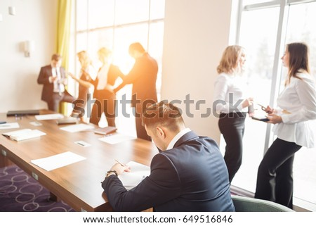 Businessman in dark suit and blue shirt sitting at office desk signing a contract with shallow focus on signature. #649516846