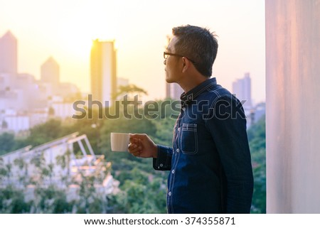 Businessman in denim jacket and glasses drinking hot coffee in sunrise.  #374355871
