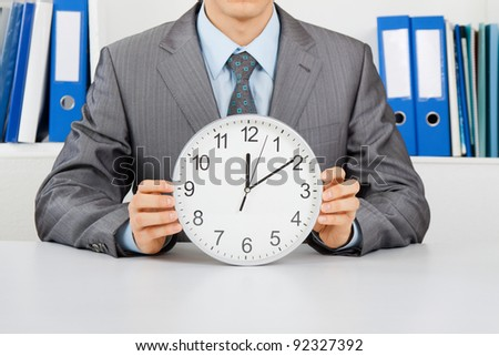 Businessman in elegant suit hold clock, sitting at the desk at office