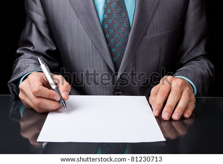 Businessman in elegant suit working with documents sign up contract, business plan sitting at desk working, concept of hold blank, empty sheet of white paper over black background. - stock photo