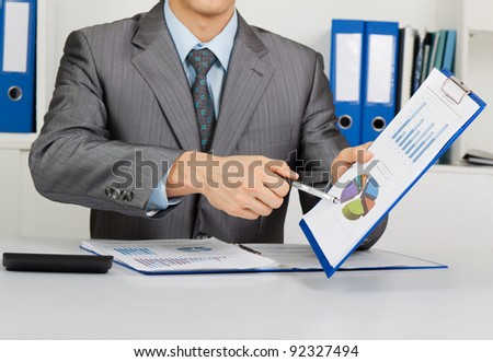 Businessman in elegant suit working with documents sign up contract, holding clipboard, folder with papers, financial business plan, sitting at the desk at office